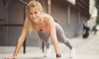 I only compete with myself. Young smiling women exercise pushups at the street.