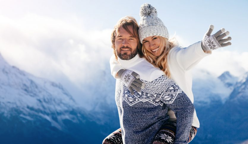 Loving couple playing together in snow outdoor. Winter holidays in mountains. Man and woman wearing knitted clothing having fun on weekends.