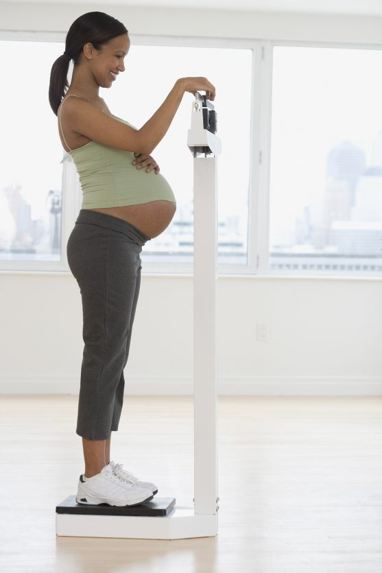 Pregnant African woman on scale