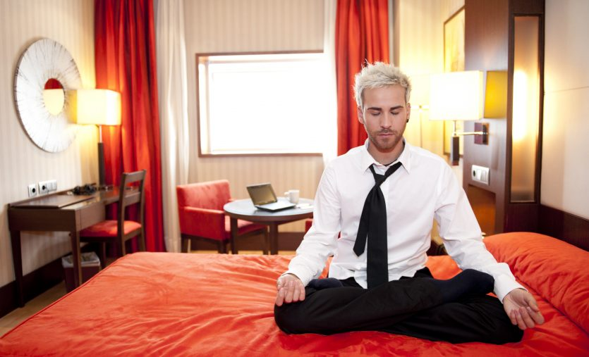 Caucasian businessman meditating in bed in lotus position.