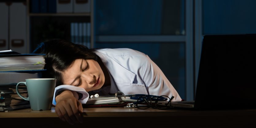 doctor feel tired sleeping on desk of clinic. beautiful mixed race asian chinese woman model. medical and health concept
