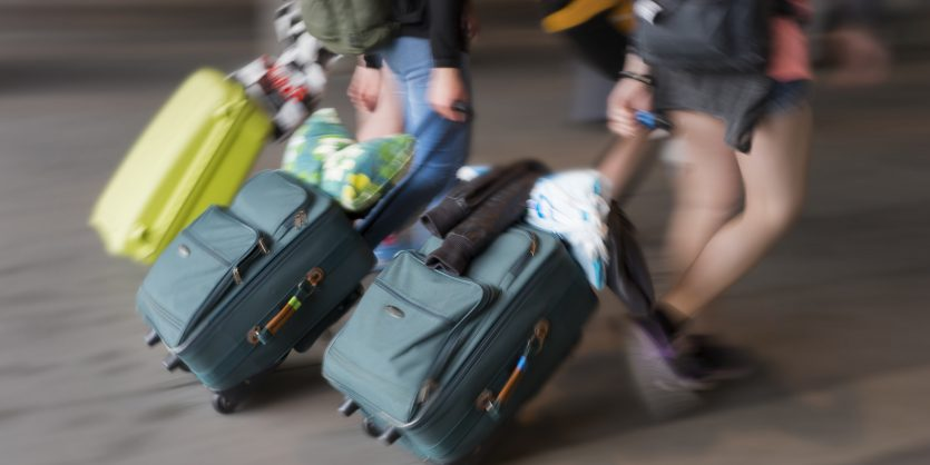 Three young persons with suitcases in blurred motion