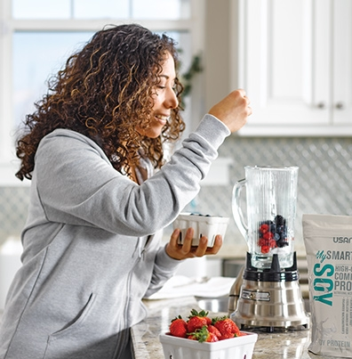 woman adding fruit to a blender