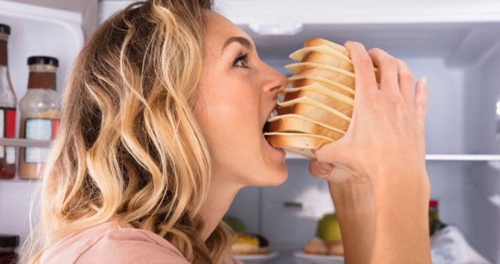 Close-up Of A Hungry Woman Eating Sandwich Near Refrigerator
