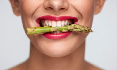 Healthy Eating. Closeup Of Woman Mouth With Beautiful Pink Lips Makeup Holding Fresh Asparagus Between White Teeth. Smiling Female Face With Vegetable In Mouth. Diet Food Concept. High Resolution
