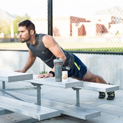muscular man doing pushup on bleachers with BiOmega bottle nearby