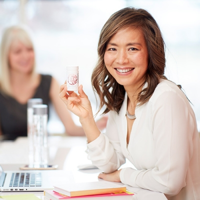 woman smiling at camera seated at computer holding bottle of EstroPro