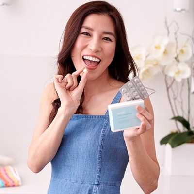 woman with beautiful smile taking oral probiotic