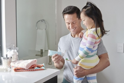father holding young daughter putting toothpaste on brush